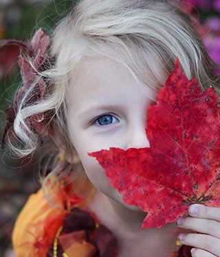 Child holding red autumn leaf | Meyer Clinic